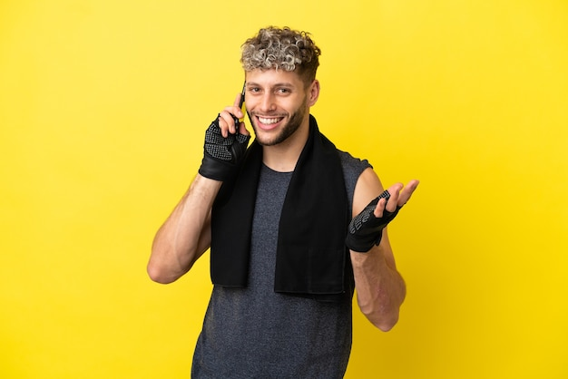 노란색 배경에 격리된 스포츠 백인 남자는 누군가와 휴대전화로 대화를 나눴다