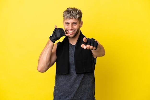 전화 제스처를 만들고 앞을 가리키는 노란색 배경에 고립 된 스포츠 백인 남자