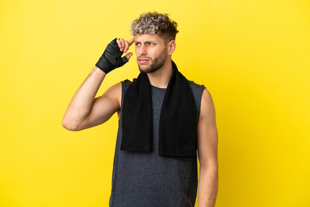 Sport caucasian man isolated on yellow background having doubts and with confuse face expression