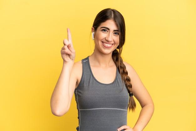 最高の兆候を示して指を持ち上げて黄色の背景に分離されたスポーツ白人女性