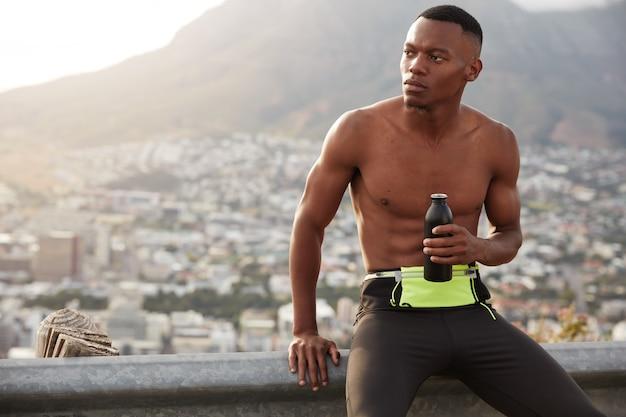 スポーツチャレンジとアクティブライフスタイルのコンセプト。男アスリートは思いやりのある表情、持久力トレーニング後の倦怠感、若返りのために真水を飲む、美しい山の景色