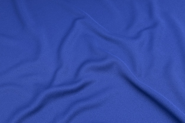Sport clothing fabric texture background. top view of cloth textile surface. blue football shirt with copyspace.
