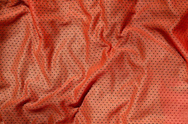 Спортивная одежда ткани текстуры фона. вид сверху из красного полиэстера