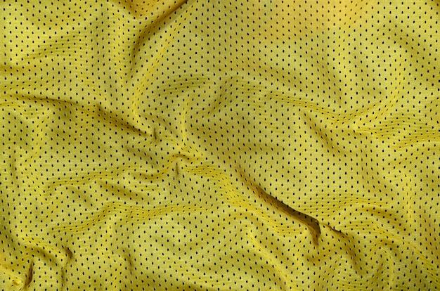 Предпосылка текстуры ткани спортивной одежды, взгляд сверху желтой поверхности ткани ткани
