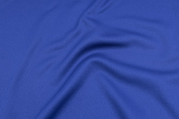 Sport clothing fabric texture top view of cloth textile surface. blue football shirt with copyspace.
