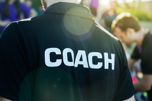 Sport coach in black shirt with white coach text on the back standing outdoor at a school