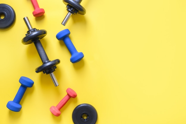 Sport colorful dumbbells on yellow.