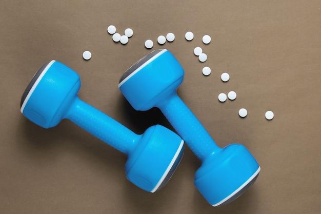 Концепция спорта. гантели, таблетки на коричневом фоне. минимализм. вид сверху