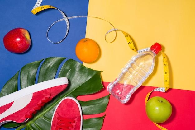 Концепция спорта. спортивные тренажеры. кроссовки, вода, яблоко, гантели на красочном фоне.