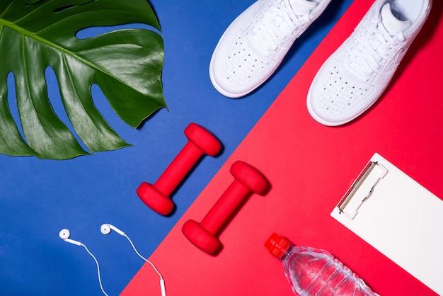 스포츠 개념입니다. 피트니스 장비. 운동화, 물, 사과, 화려한 배경에 아령.