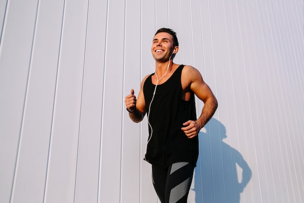 Sport concept. smiling handsome muscular guy running outdoors, against the white wall