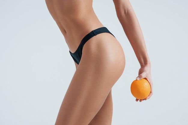 Концепция спорта. фотография девушки в нижнем белье, держащей апельсин в руке.