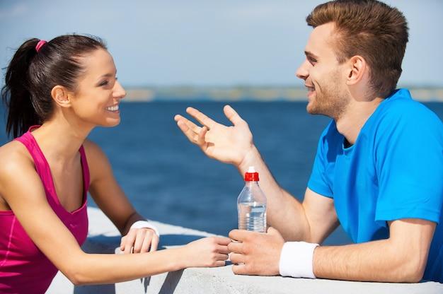 Спорт объединяет людей. вид сбоку красивой молодой пары в спортивной одежде, стоящей лицом к лицу и разговаривающей