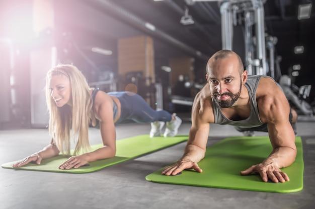 Спортивная пара делает тренировку тренировки планки в фитнес-центре. мужчина и женщина практикуют планку в тренажерном зале.