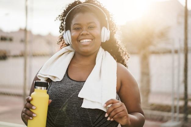 Спортивная фигуристая черная женщина слушает музыку в наушниках