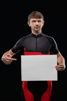 Sport. cyclist in training clothes on black background holding blank sheet of paper. your text here.