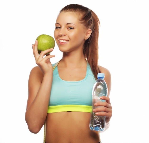 Sport, diet, health and people concept with  young cheerful woman in sports wear with apple and a bottle of water