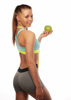 Sport, diet, health and people concept: young cheerful woman in sports wear with apple, isolated over white background