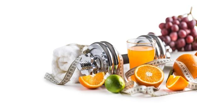 Спортивная лента измерения свежих фруктов гантелей и поливитаминный сок, изолированные на белом фоне. концепция здорового спорта и диеты.