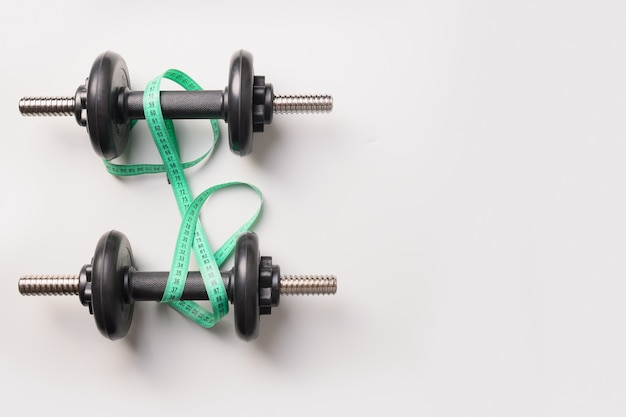 Sport dumbbells and measuring tape on grey background. top view, copy space.