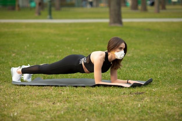 検疫中のスポーツ。屋外トレーニング若い運動女性。彼女は医療用マスクを着ています。 covid19。コロナウイルス。