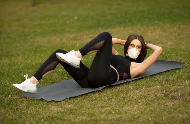 격리 중 스포츠. 젊은 운동 여자 야외 훈련. 그녀는 의료 마스크를 쓰고있다. 코로나 19. 코로나 바이러스.