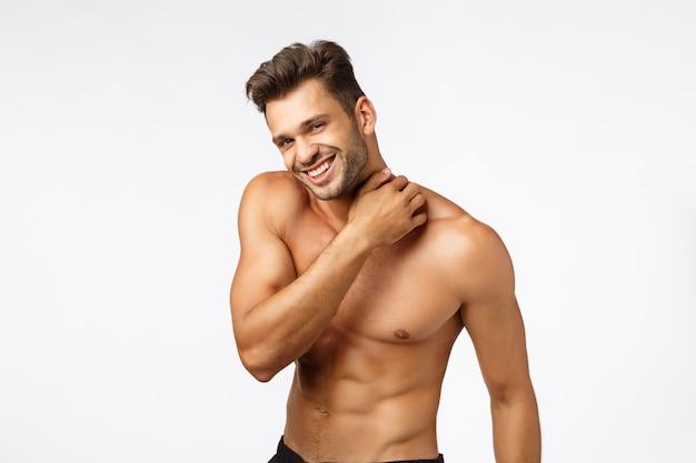 スポーツ、感情、美容のコンセプト。 6パックでハンサムな幸せな若いスポーツマン
