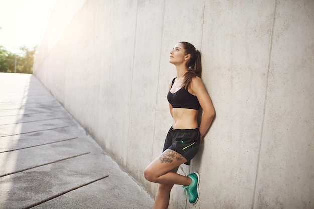 Sport, endurance and athlete concept. healthy and active dreamy young sportswoman in sportsbra and shorts, lean on wall, looking up sky, rest after jogging workout, outdoor maraphon practice. Premium Photo