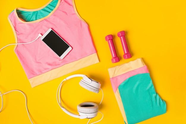 노란색 배경 상단 보기에 휴대 전화가 있는 스포츠 장비 및 의류