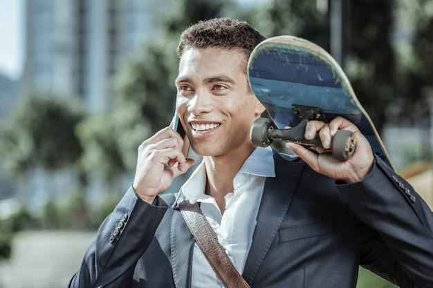 Sport equipment. exuberant male student holding skateboard and speaking on phone