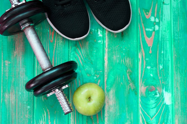 Sport equipment - green apple,bottle of water, pair of pink dumbbells and black towel on mint background.