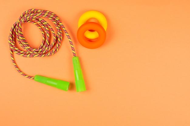 Спортивное оборудование на оранжевом фоне. скопируйте пространство.