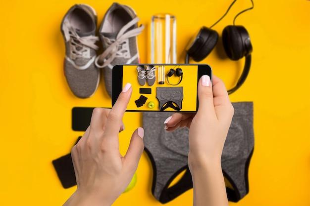 携帯電話で撮影するスポーツ用品。フィットネスツールの画像とスマートフォンの画面。ソーシャルネットワーク向けに作成