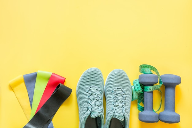 Sport equipment, rubber band, dumbbells, fitness shoes, measuring tape on yellow.