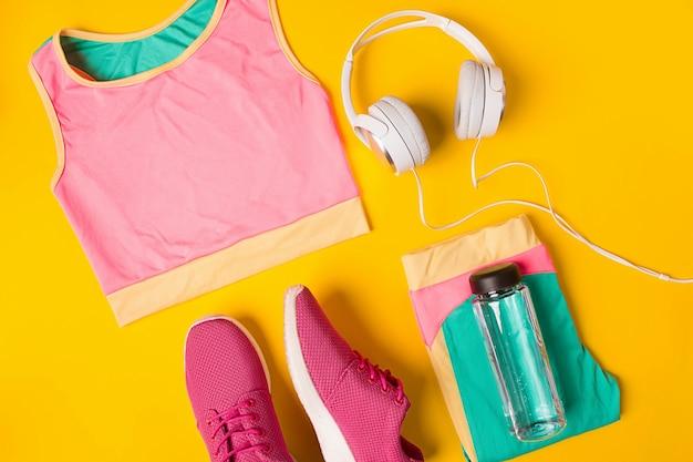 黄色の背景にスポーツ用品スニーカーと水のボトル