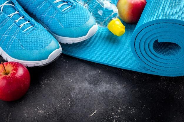 Sport equipment sport shoes, yoga mat, apples, bottle of water.