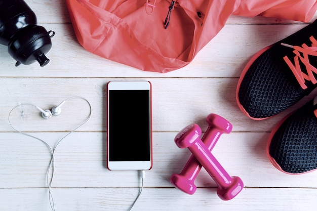 Sport equipment with empty screen smart phone on white wooden background