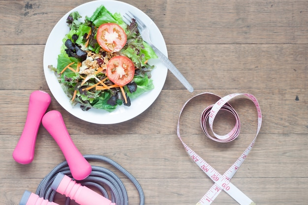 Sport equipments, fresh salad and measuring-tape in heart shape, healthy lifestyle concept