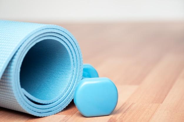 Спортивное оборудование на размытом фоне. силовые упражнения. спортивный коврик и гантели на полу. тренировка дома. домашние упражнения. здоровый образ жизни. период изоляции. силовая тренировка. концепция карантина.