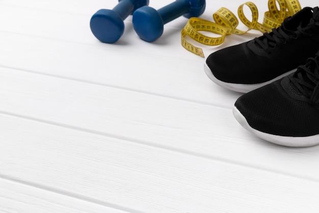 スポーツ機器、スニーカー、白い木製の背景に巻尺。パーソナルフィットネスプログラムトレーニングコンセプト