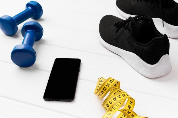 Sport equipments, sneakers and tape measure on white wooden surface