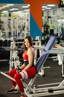 Sport everyday. young healthy woman working out at gym. doing exercises on the simulator