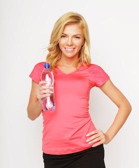 スポーツ、運動、ヘルスケア-水のボトルとスポーティな金髪の女性