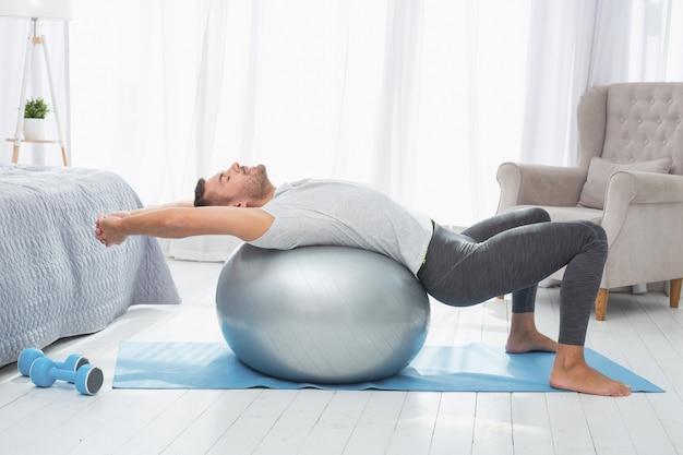 Спортивные упражнения. красивый хорошо сложенный мужчина, лежа на медицинском мяче во время тренировки