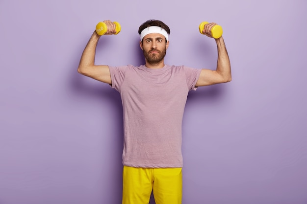 Sport, exercising and motivation concept. serious unshaven man raises arms with dumbbells, dressed in purple t shirt and yellow shorts, wants to be healthy and strong