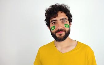 スポーツファン、カメラを見て笑う。彼の顔にブラジルのメイクの旗を持つ男。