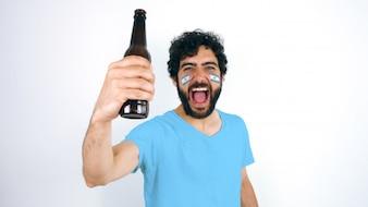 アルゼンチンの旗を掲げたスポーツファンが、ビールを持って彼の顔にハイヒールの勝利を叫びました