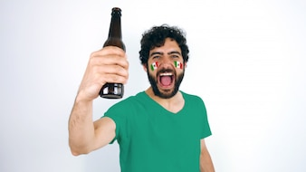 Sport fan with Mexico flag on his face holding a beer screaming for the triumph of his tea