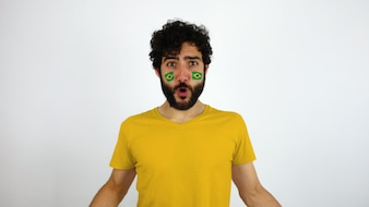 Sport fan with the Brazil flag makeup on his face celebrating a goal of his team