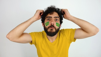 Sport fan with the flag of Brazil makeup on his face disappointed with his team
